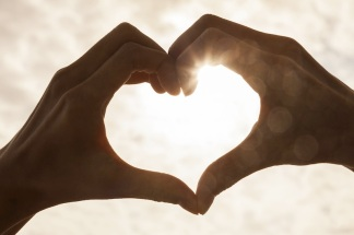 Hand heart shape silhouette made against the sun & sky of a sunr